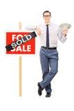 Agente inmobiliario masculino que sostiene el dinero al lado de una muestra vendida Foto de archivo