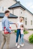 agente inmobiliario masculino sonriente con la muestra vendida que da llave a la mujer joven fotos de archivo libres de regalías