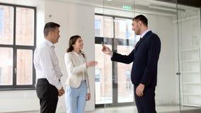 Agente inmobiliario que da llave a los clientes en la nueva oficina almacen de video