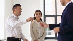 Agente inmobiliario que da llave a los clientes en la nueva oficina metrajes