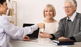 Agente inmobiliario que da llave madura de los pares a la nueva casa imagen de archivo libre de regalías