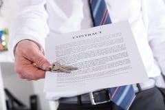 Agente inmobiliario que da llaves con el contrato Foto de archivo