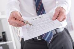 Agente inmobiliario que da llaves con el contrato Fotografía de archivo libre de regalías