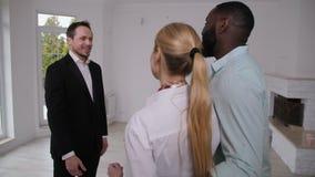 Agente inmobiliario que da llaves de la casa a la pareja de matrimonios feliz almacen de video