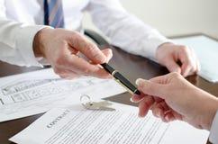 Agente inmobiliario que da una pluma para la firma Fotos de archivo
