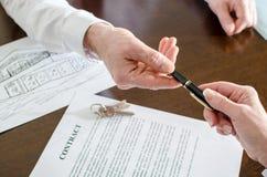 Agente inmobiliario que da una pluma para la firma Fotos de archivo libres de regalías