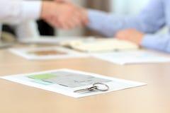 Agente inmobiliario que firma un contrato Apretón de manos Una llave de la casa con proyecto de un plano detrás Foto de archivo libre de regalías