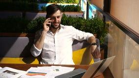 Agente inmobiliario que habla por smartphone y que trabaja con el ordenador portátil en la tabla almacen de metraje de vídeo