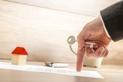 Agente inmobiliario que lleva a cabo llave de la casa mientras que muestra con su finge Fotografía de archivo libre de regalías