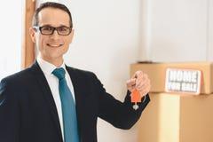 Agente inmobiliario que lleva a cabo llaves con el icono de la casa en el nuevo apartamento con las cajas de cartón fotos de archivo