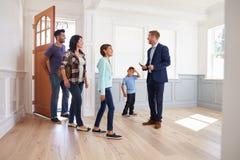 Agente inmobiliario que muestra a la familia hispánica alrededor de nuevo hogar imagen de archivo