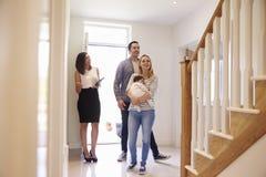 Agente inmobiliario que muestra a la familia joven alrededor de la propiedad para la venta Foto de archivo