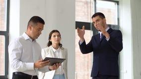Agente inmobiliario que muestra la oficina a los clientes con PC de la tableta metrajes