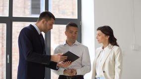 Agente inmobiliario que muestra la oficina a los clientes con PC de la tableta almacen de video