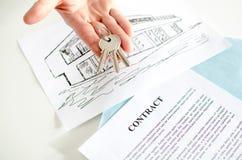 Agente inmobiliario que muestra llaves de la casa Foto de archivo