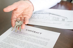 Agente inmobiliario que muestra llaves de la casa Fotos de archivo libres de regalías
