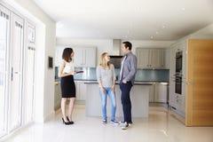 Agente inmobiliario que muestra pares jovenes alrededor de la propiedad para la venta imagenes de archivo