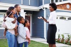 Agente inmobiliario que muestra a una familia una casa, más cercana adentro fotos de archivo