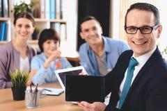 Agente inmobiliario que se sienta en el escritorio en oficina El agente inmobiliario está presentando la tableta con la familia e fotos de archivo libres de regalías