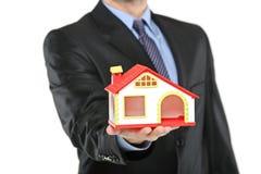 Agente inmobiliario que sostiene una casa modelo en una mano Fotos de archivo libres de regalías