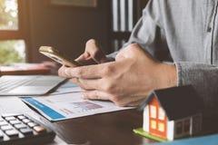 Agente inmobiliario que trabaja con el teléfono, el ordenador portátil y el documento elegantes o imagen de archivo libre de regalías