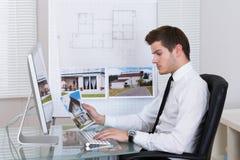 Agente inmobiliario que trabaja en el ordenador Fotos de archivo libres de regalías
