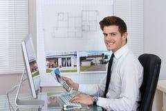 Agente inmobiliario que trabaja en el ordenador Imágenes de archivo libres de regalías