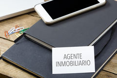 Agente inmobiliario, Spanish text for Realtor business card on o. Agente inmobiliario, Spanish text for Realtor, business card on office desktop with notebooks Stock Photos