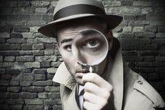 Agente investigativo d'annata che guarda tramite una lente Fotografia Stock Libera da Diritti