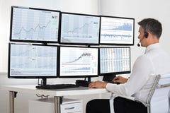 Agente Looking At Graphs del mercado de acción en las pantallas múltiples fotos de archivo libres de regalías