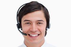 Agente masculino sonriente del centro de atención telefónica con el receptor de cabeza encendido Foto de archivo