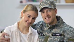 Agente militar hermoso que abraza a la esposa bonita, amor joven de los pares, nación americana almacen de video
