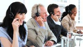 Agente moreno feliz do centro de chamada que trabalha com seus colegas vídeos de arquivo