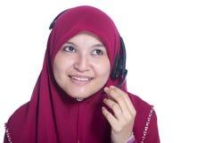 Agente musulmán hermoso joven del servicio de atención al cliente de la mujer con las auriculares en el fondo blanco Imagenes de archivo