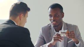 Agente negro inmobiliario con el contrato de firma del hombre en la oficina blanca metrajes