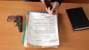 Agente segreto, spia, con una pistola nell'ufficio che cerca informazioni, archivi, documenti video d archivio
