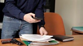 Agente segreto, spia, con una pistola nell'ufficio che cerca informazioni, archivi, documenti stock footage