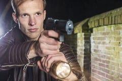 Agente speciale con la pistola di servizio e torcia in vicolo Fotografia Stock