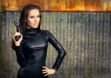 Agente Woman del espía en el traje de cuero negro que sostiene el arma Foto de archivo