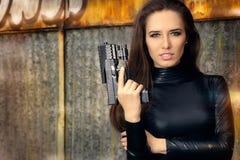 Agente Woman del espía en el traje de cuero negro que sostiene el arma Imagen de archivo libre de regalías