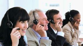 Agentes alegres del centro de llamada que se sientan mientras que lleva las auriculares almacen de video