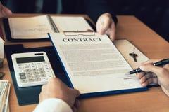 Agentes caseros que hablan con los compradores de vivienda que están firmando contratos en la oficina foto de archivo libre de regalías