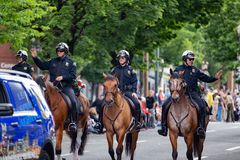 Agentes da polícia montados cavalo que andam abaixo da rua fotografia de stock