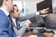 Agentes de bolsa que miran las pantallas de ordenador, negociando en línea fotografía de archivo libre de regalías