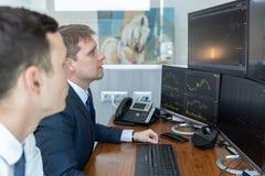 Agentes de bolsa que miran las pantallas de ordenador, negociando en línea foto de archivo