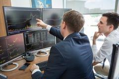 Agentes de bolsa que miran las pantallas de ordenador, negociando en línea fotografía de archivo