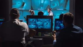 Agentes de segurança que olham as câmaras de vigilância video estoque