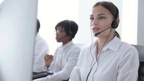 Agentes del centro de atención telefónica que consultan a clientes en la línea directa en la oficina almacen de metraje de vídeo
