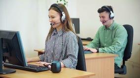 Agentes del centro de llamada que trabajan en su oficina brillante almacen de video