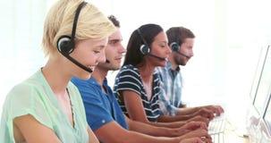 Agentes felices del centro de llamada que hablan en las auriculares metrajes